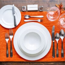 A place setting on an orange placemat.