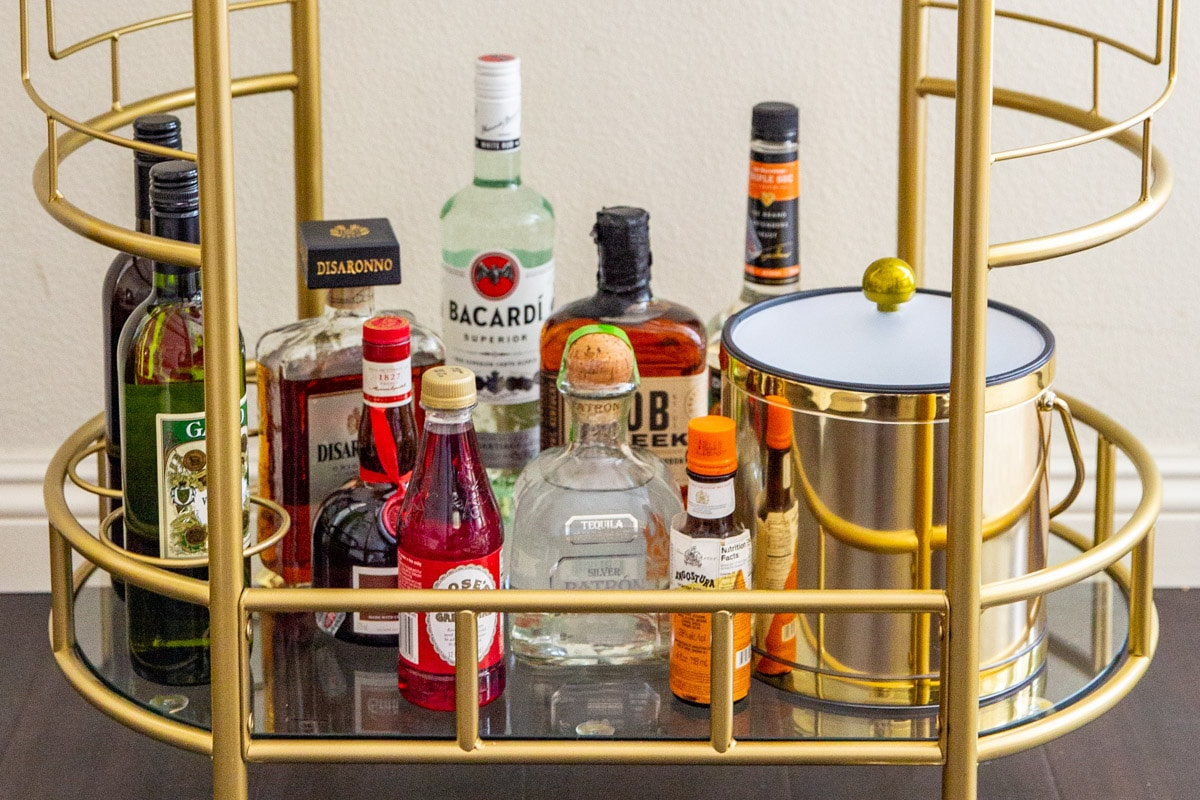 The bottom tier of a stocked bar cart.