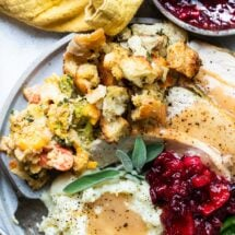 A plate of roasted trukey, stuffing, vegetables, mashed potatoes and gravy, and cranberries.