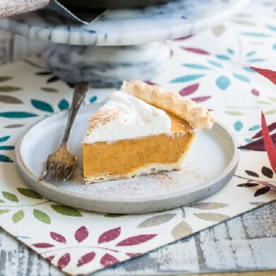 A slice of pumpkin pie on a table with the rest of the pie in the background.