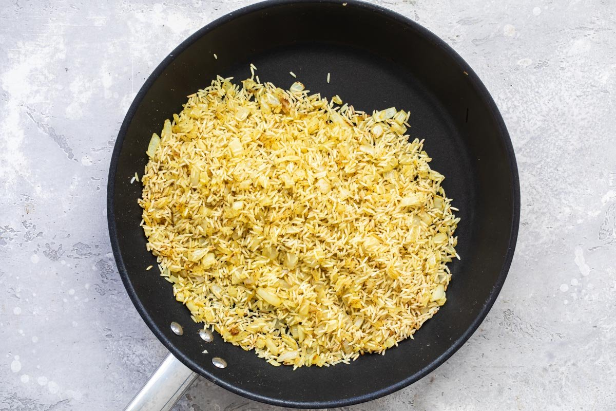 Rice toasting in a skillet.