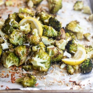 Roasted broccoli on a baking sheet with lemon garnish.