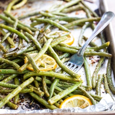 Oven roasted green beans on a baking sheet with a lemon garnish.