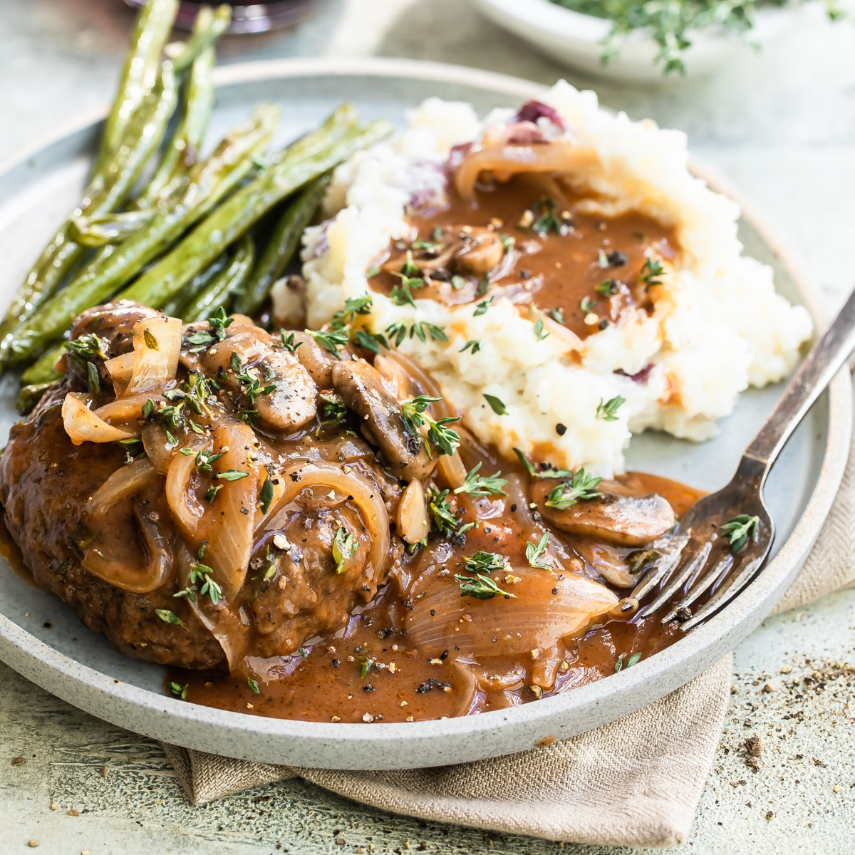 A salisbury steak on a plate with mashed potatoes, gravy, and green beans.