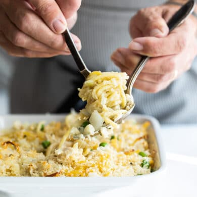 Turkey tetrazzini being scooped out of a white baking dish.