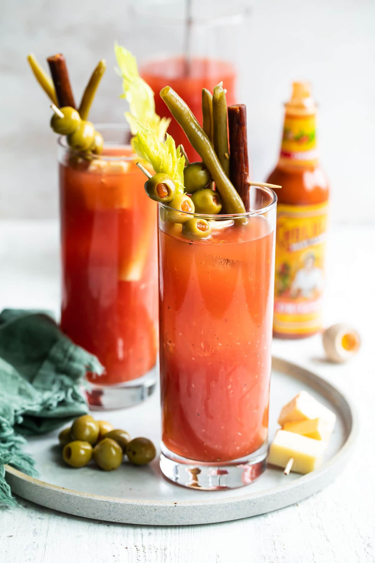 Two bloody marys with garnishes.