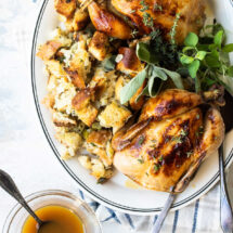 Two cornish hens with stuffing on a serving platter.