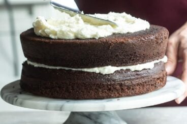 Buttercream frosting being spread on a chocolate layer cake.