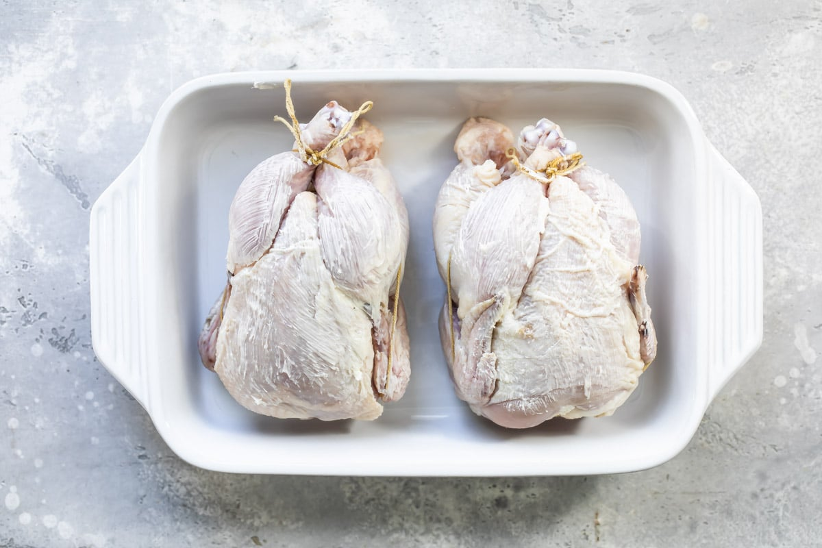 Two unbaked Cornish hens in a baking dish.