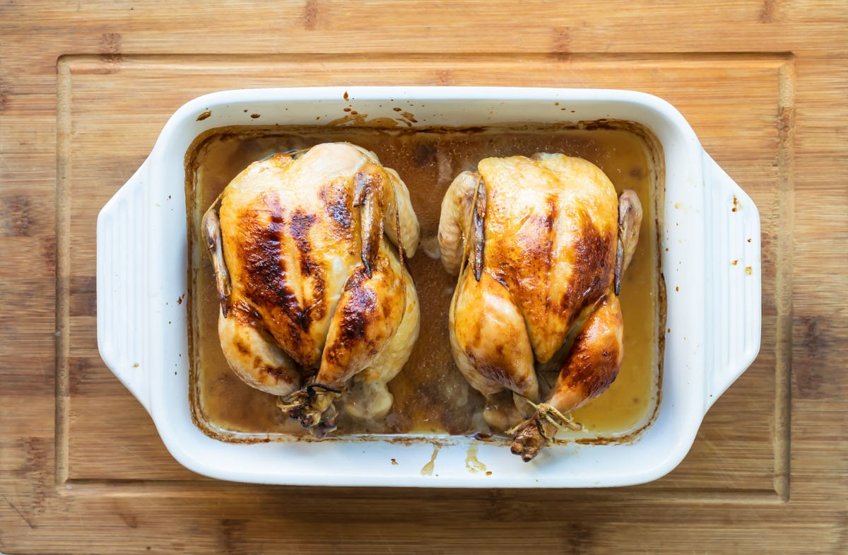 Two cooked Cornish hens in a baking dish.