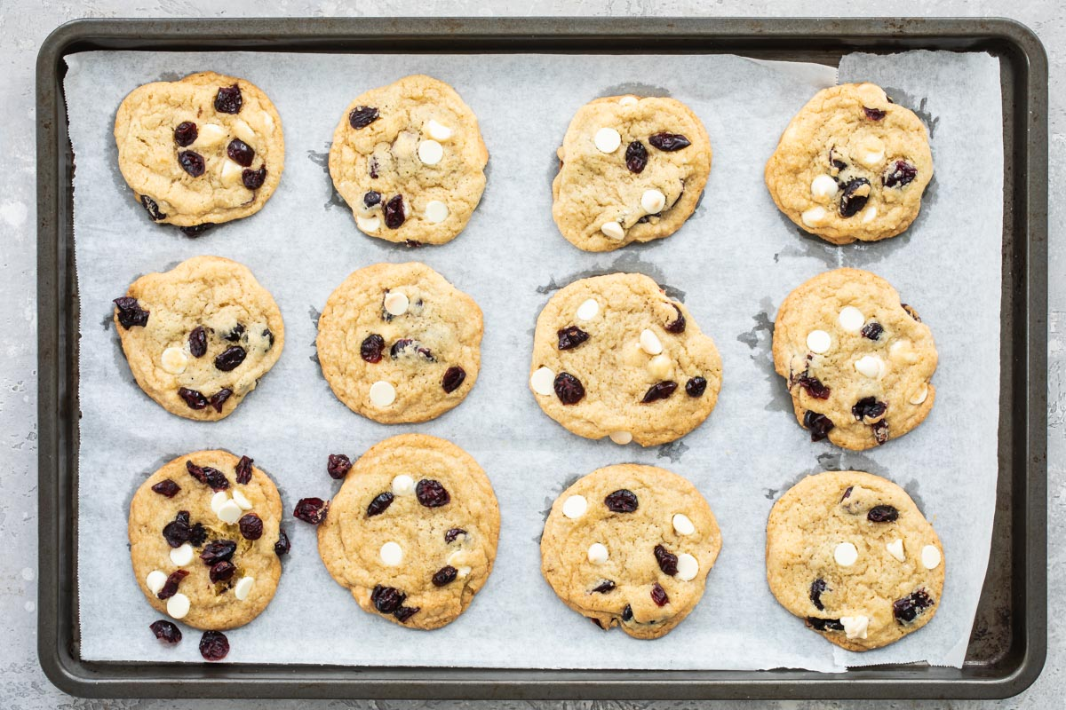 Cranberry cookies with white chocolate on a baking sheet.