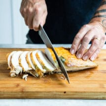 Carving roasted turkey breast into slices.