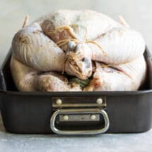 A raw trussed turkey in a roasting pan.