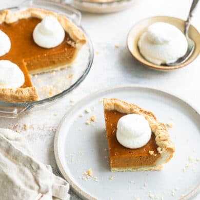 A slice of mini pumpkin pie on a white plate with a mini pumpkin pie and whipped cream behind it.