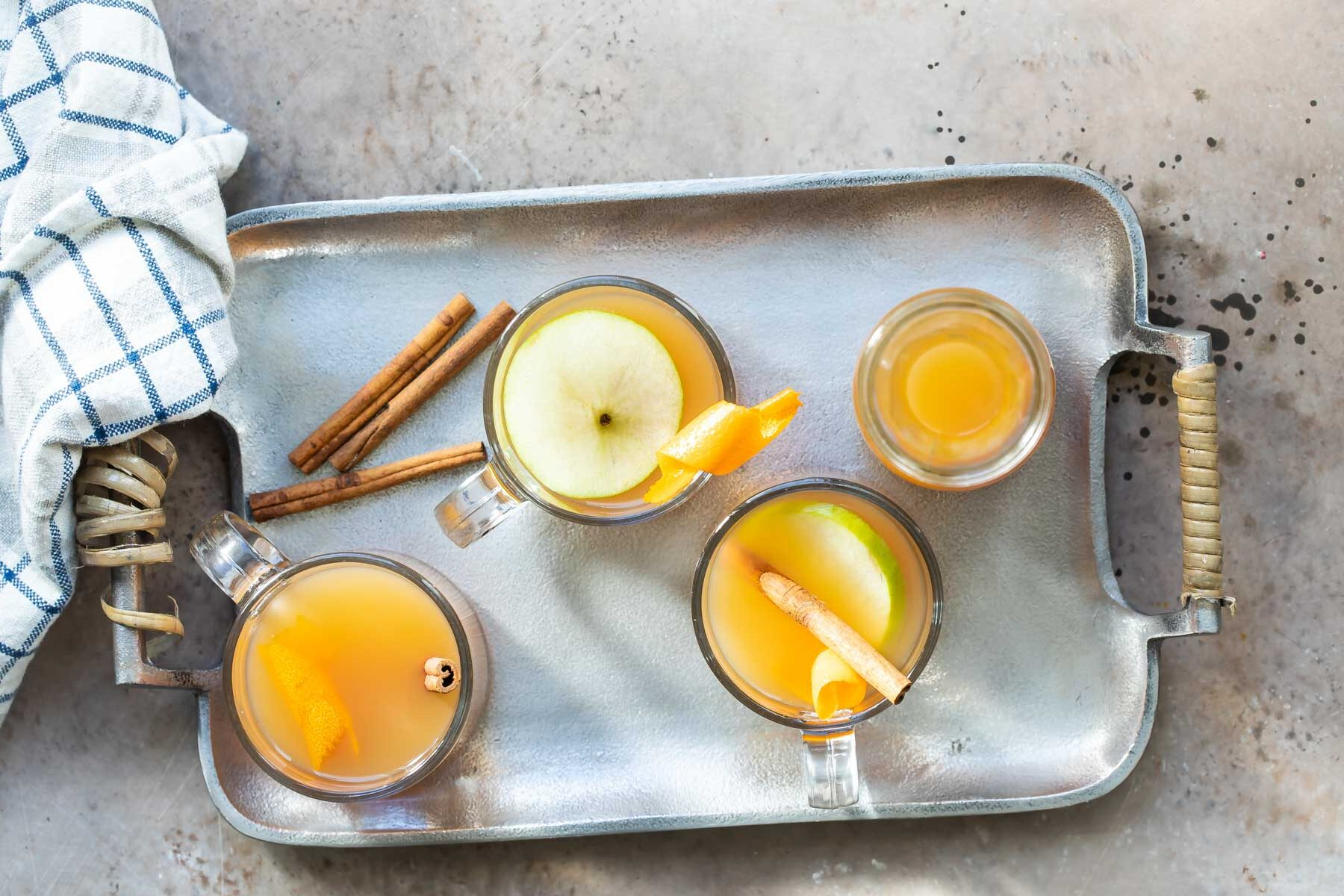 Three glasses and a carafe of mulled cider on a silver serving platter.