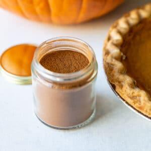 Pumpkin pie spice in a jar next to a pumpkin pie.