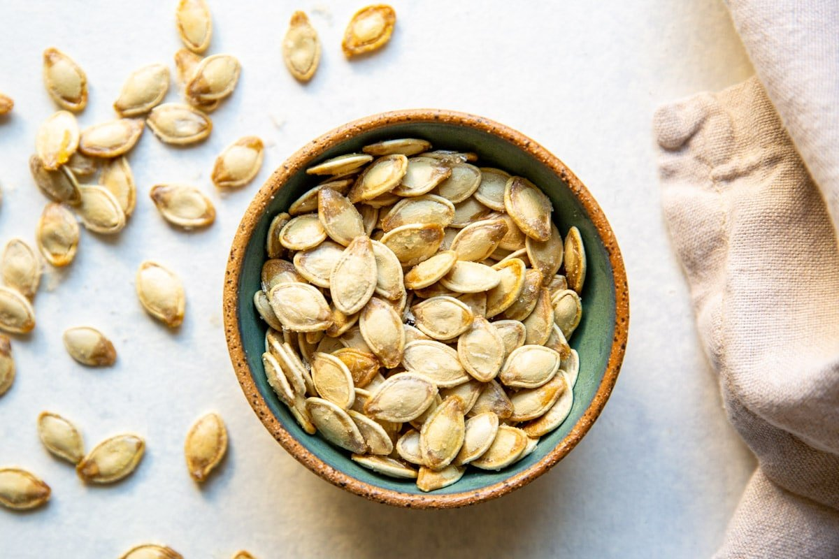 Roasted pumpkin seeds in a brown and teal bowl.