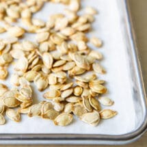 Pumpkin seeds on top of parchment paper on a baking sheet.