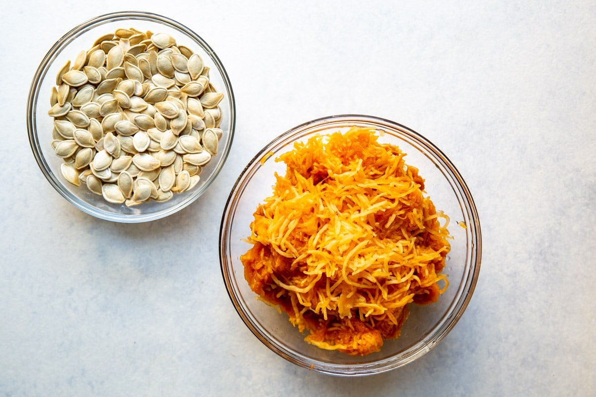 Pumpkin puree in a clear bowl next to pumpkin seeds in a clear bowl.