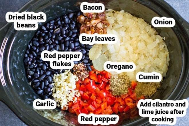 Labeled slow cooker black bean ingredients in a crock pot.