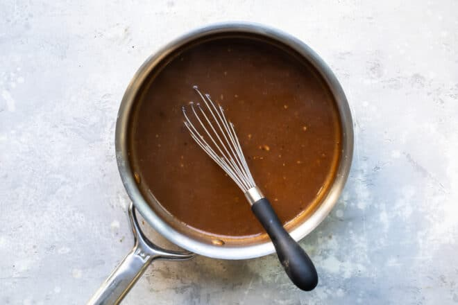 Pot roast gravy in a saucepan.