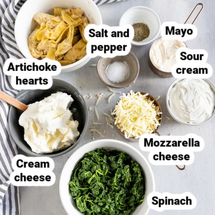 Labeled spinach artichoke dip ingredients in various bowls.