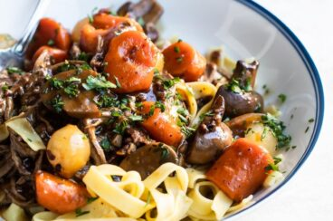 Beef Bourguignon over egg noodles in a white bowl.