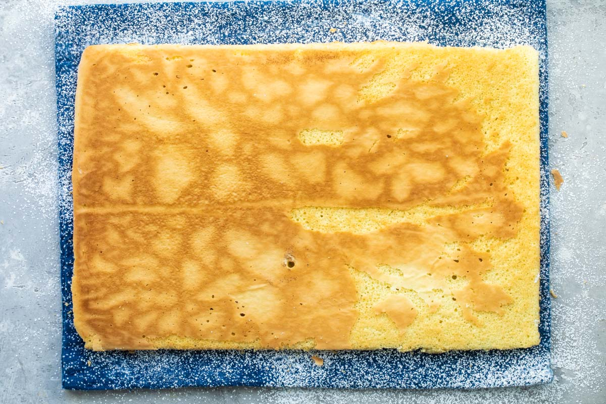 A baked roll cake lying flat on a kitchen towel before being rolled.