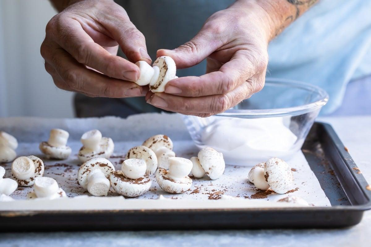 Meringue mushrooms piped on a baking sheet.
