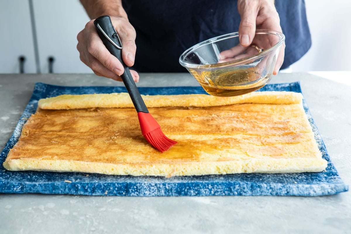Rum syrup being brushed over a roll cake.