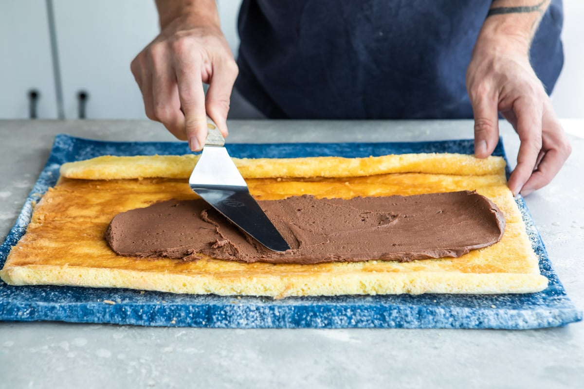 Chocolate frosting being spread over a roll cake.