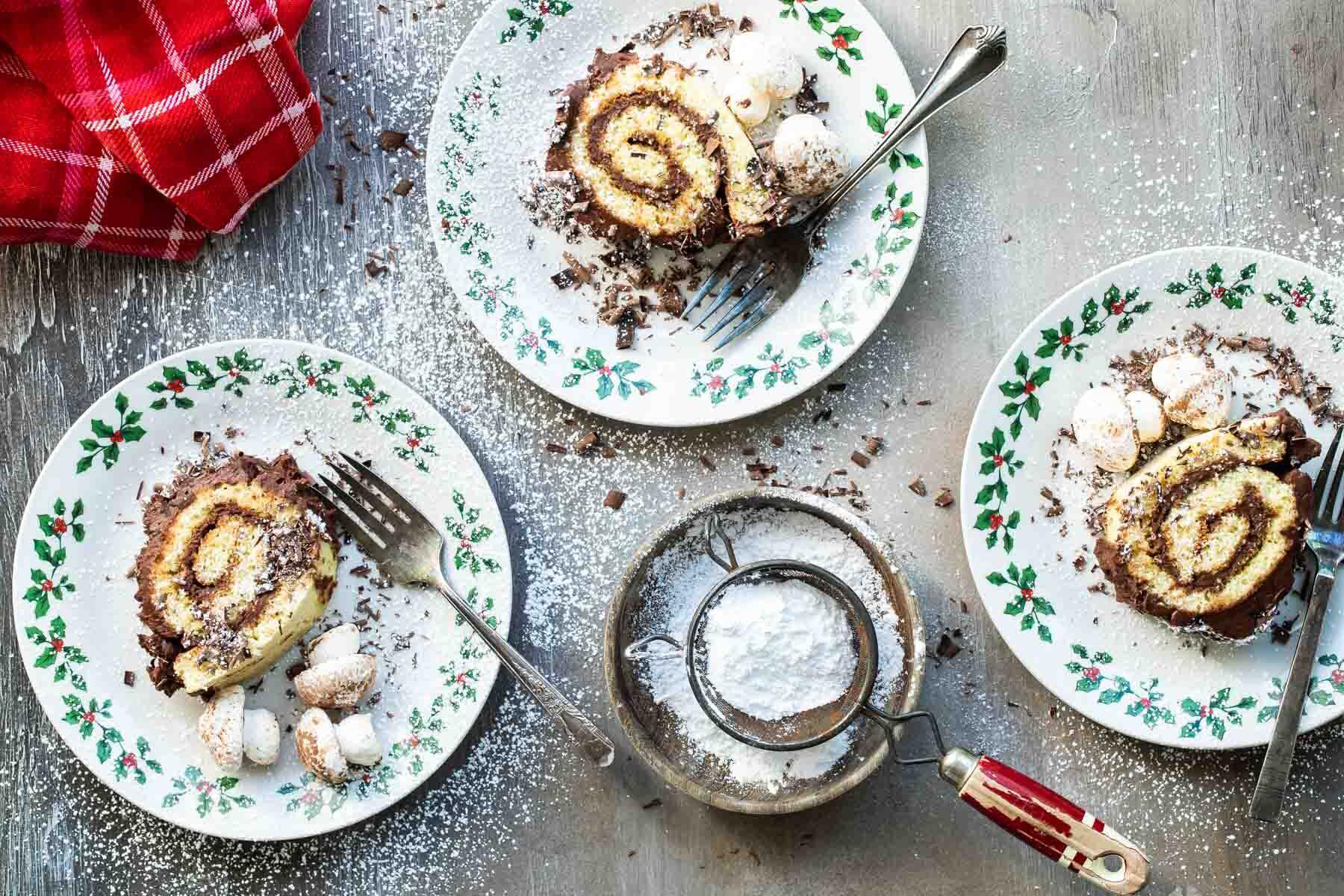 3 slices of Buche de Noel (yule log cake) on plates.