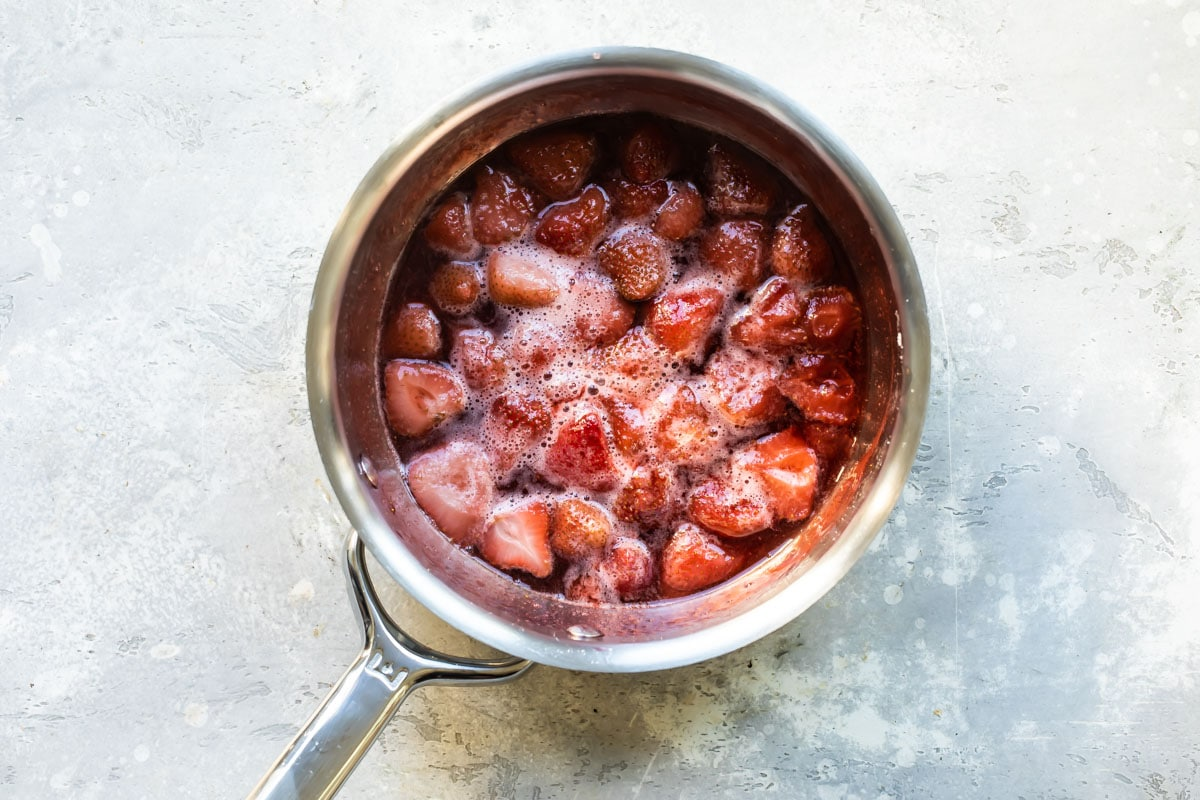 Frozen strawberries in a saucepan with water and sugar.