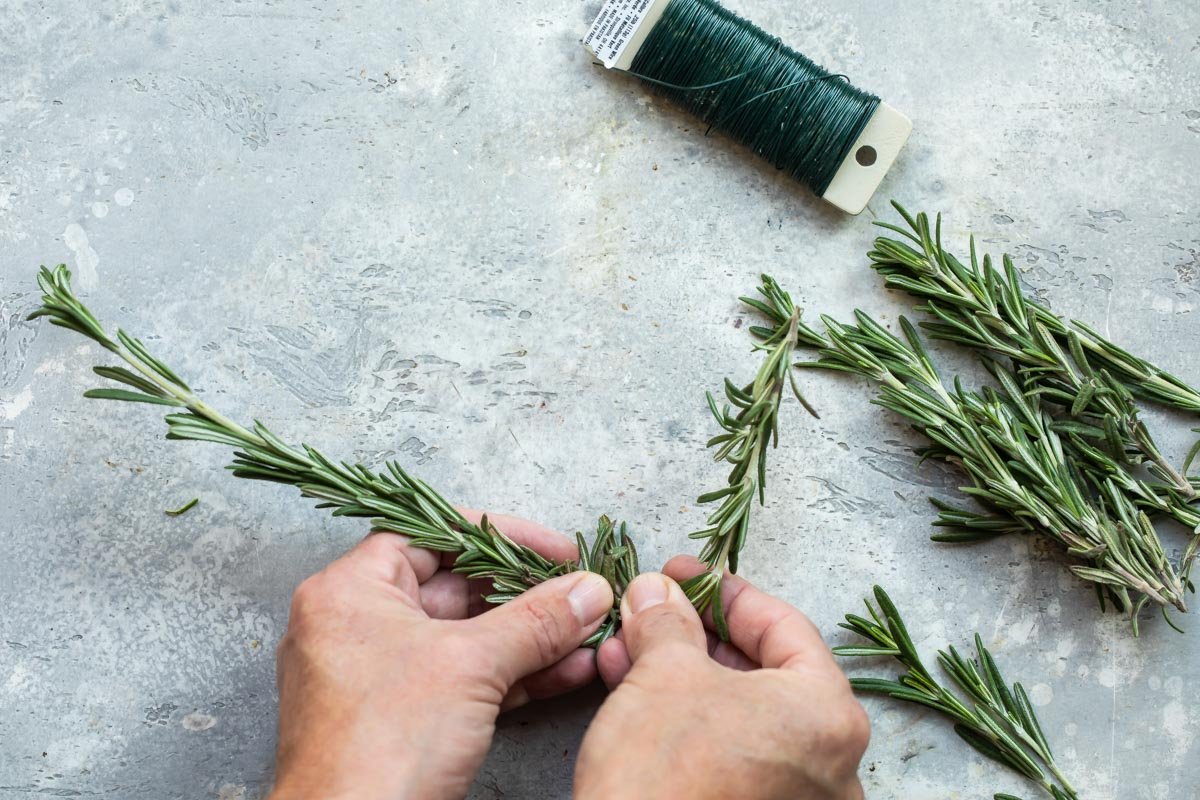 Someone forming a wreath out of rosemary with floral wire.