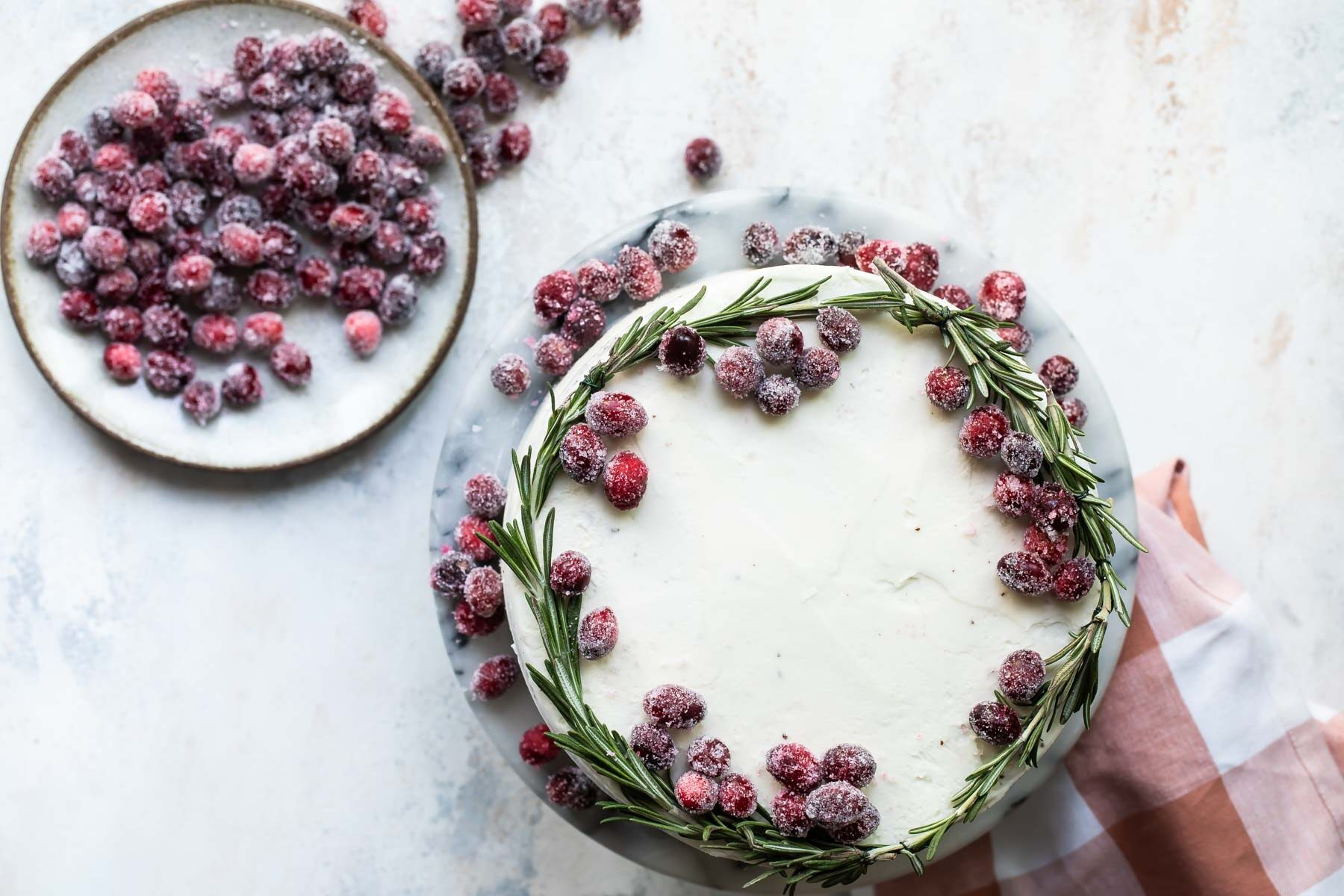 A cranberry wreath cake on a granite cake platter with a small plate of sugared cranberries next to it.