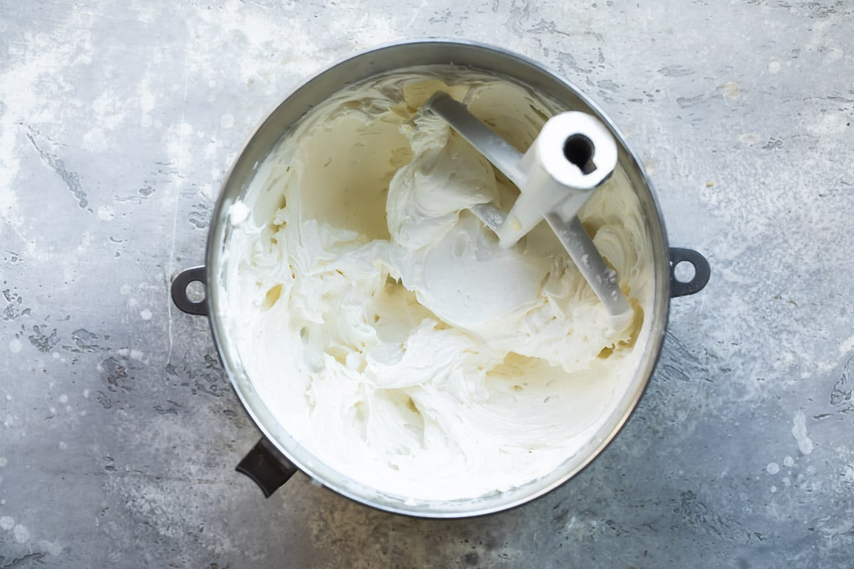 Buttercream frosting in a silver mixing bowl.