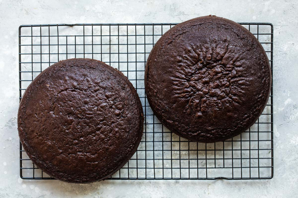 Two round chocolate cakes on a cooling rack.