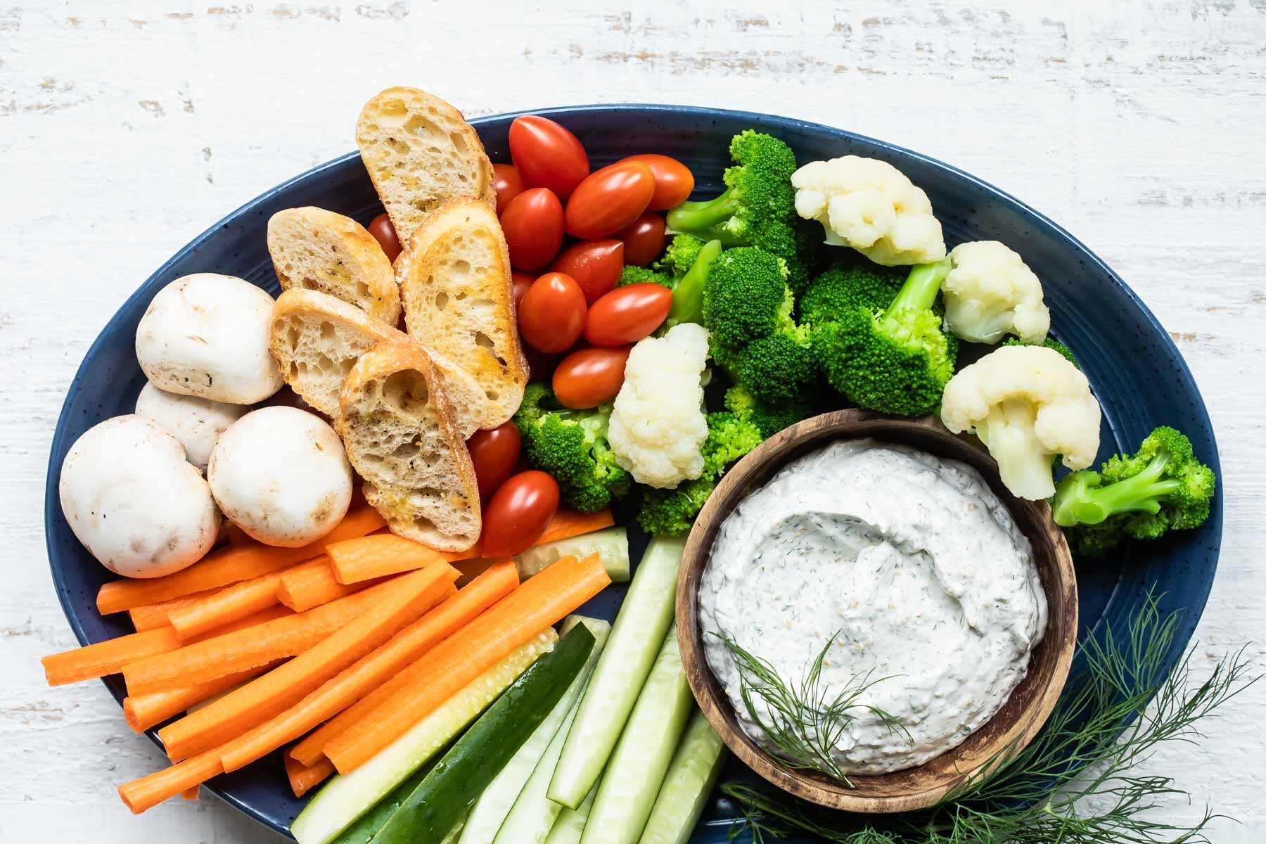 A platter with dill dip and fresh vegetables.