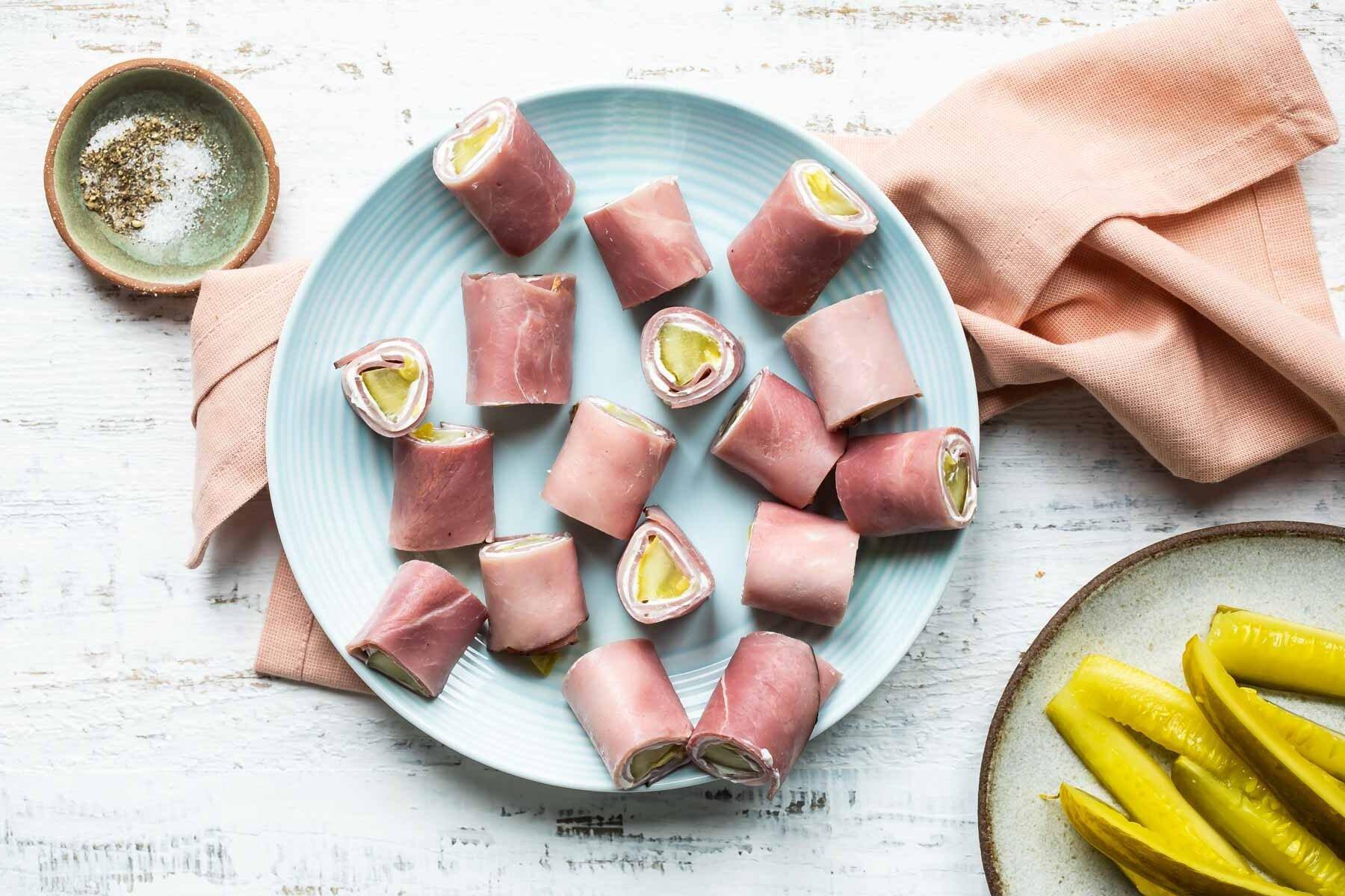 Ham roll ups on a light blue plate.