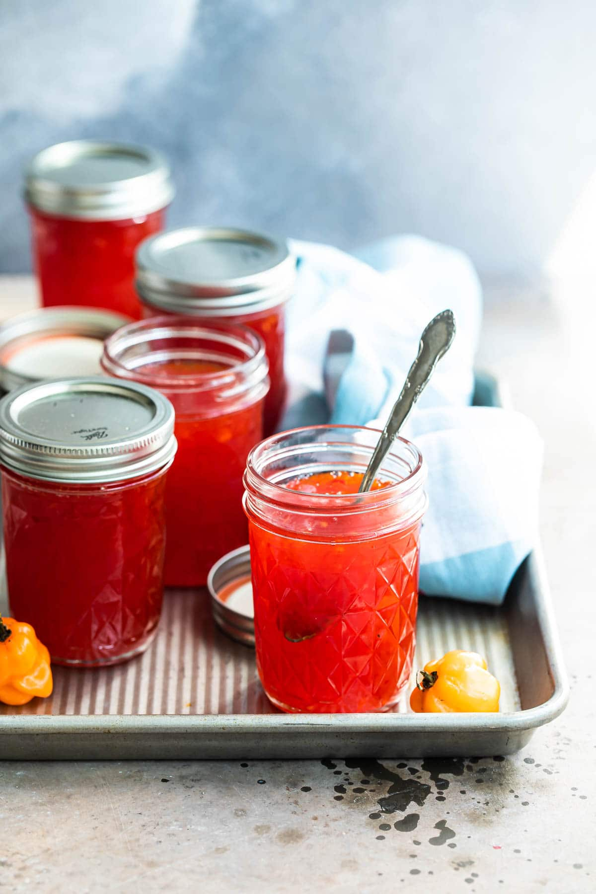 Jars of red pepper jelly on a tray.