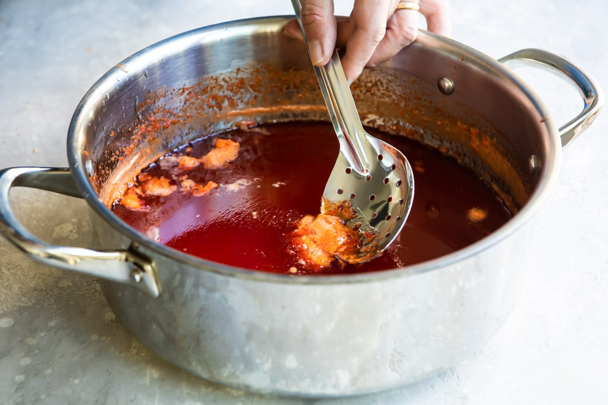 Skimming the foam off a pan of pepper jelly.