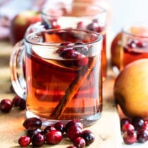 Slow cooker cranberry apple cider in a clear mug.