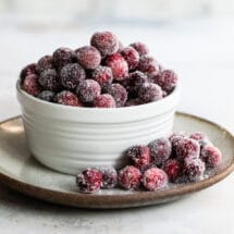 Sugared cranberries in a small white bowl.