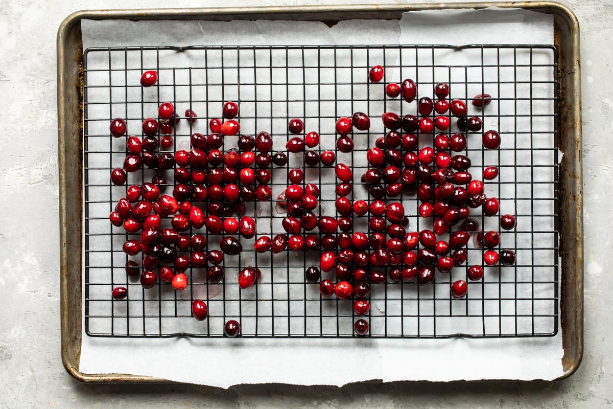 Cranberries on a cooling rack over parchment paper.