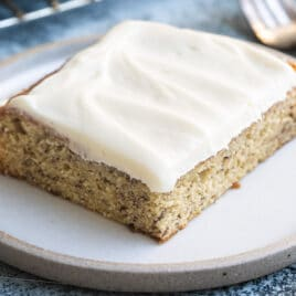 A slice of banana cake with cream cheese frosting on a white plate with a fork next to it.