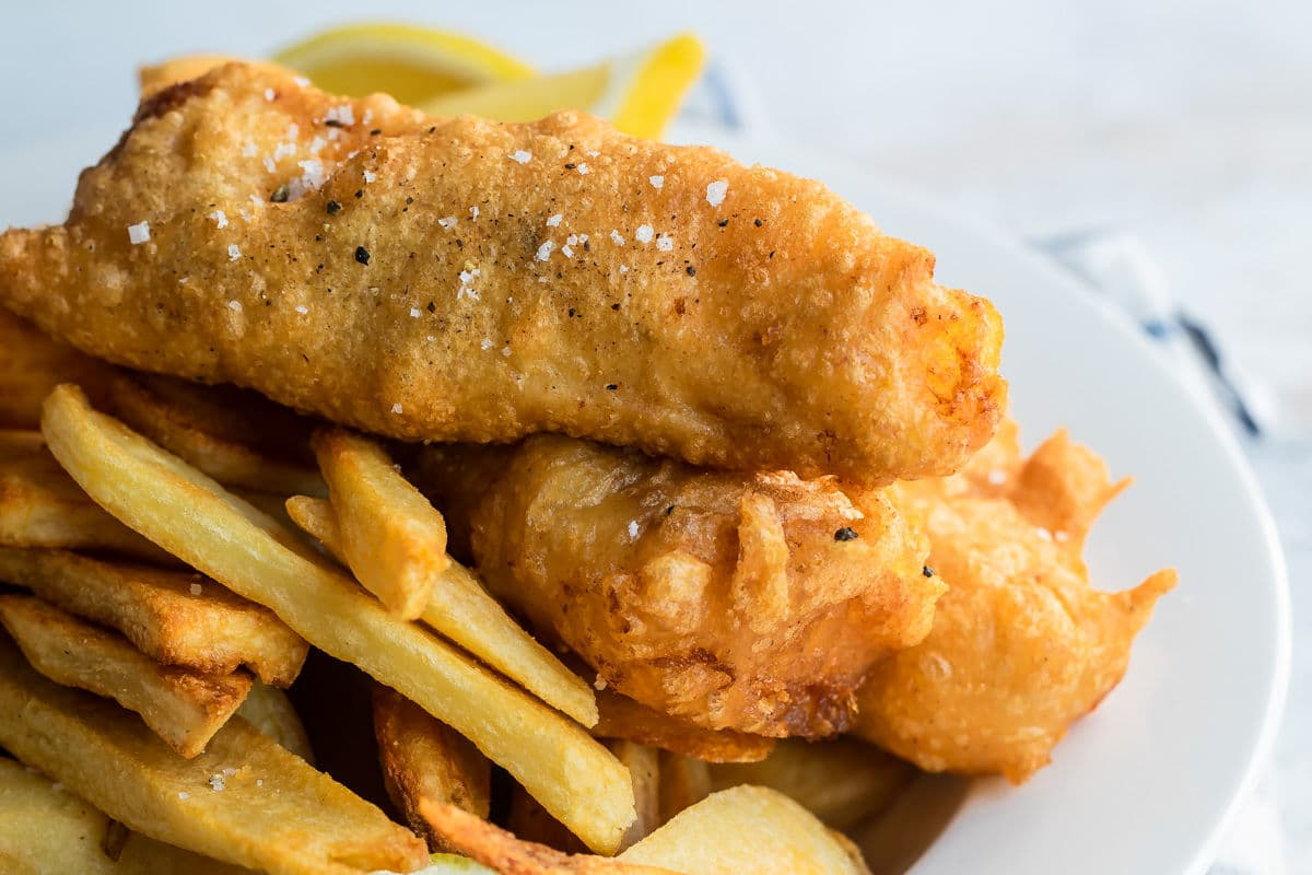Beer battered cod, fries, tartar sauce and a lemon wedge on a plate.