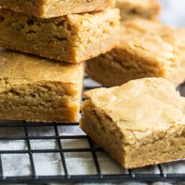 A stack of blondies on a cooling rack.