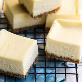 Cheesecake bars on a cooling rack.