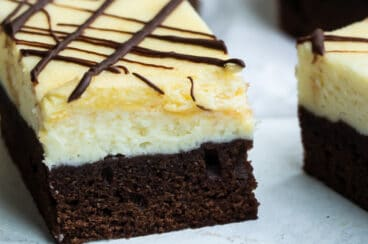 Cheesecake brownies on a white plate.