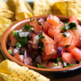 Chipotle tomato salsa in a black bowl on a blue plate with tortilla chips.